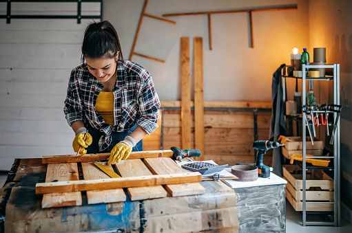 Young, female adult practising carpentry skills and measuring planks of wood